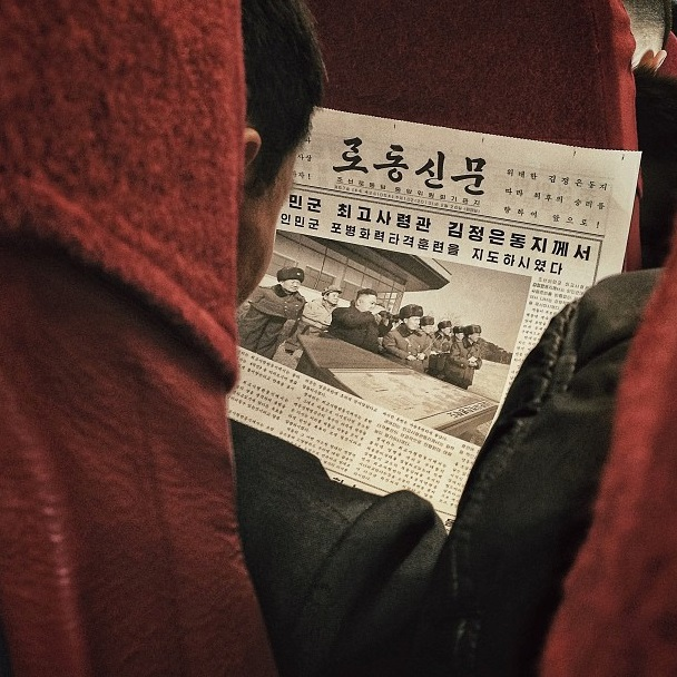 A North Korean passenger aboard a North Korean Air Koryo flight from Pyongyang to Beijing reads a newspaper article about leader Kim Jong Un. Instagram image by David Guttenfelder