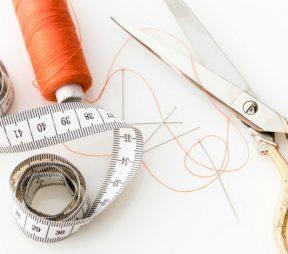 Scissors cutting string beside measuring stick.