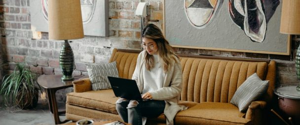 young woman typing on laptop while sitting on funky couch