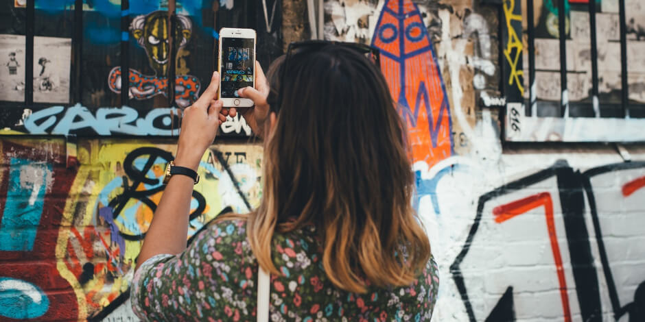 girl making an instagram story of a graffiti wall