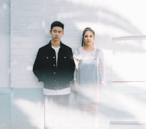 Two hip, young people (a boy and a girl) standing in front of a white wall outside in the sunshine