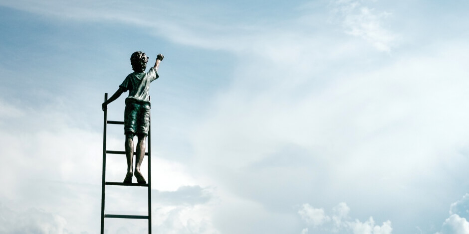 boy climbing ladder in sky