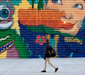 person walking by a colorful mural on the street