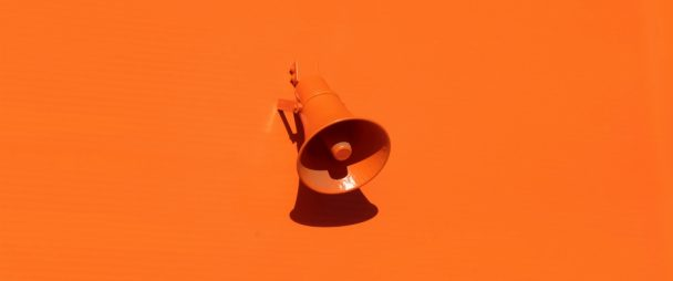Orange megaphone on an orange wall