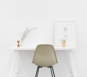 white desk against white wall with white chair