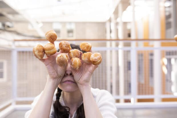 person holding mini doughnuts on each finger
