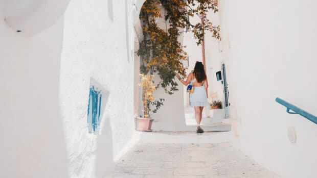 traveller walking through the white alleyways of Greece
