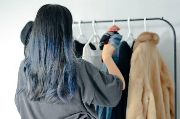 retail stylist arranging coats on hangers