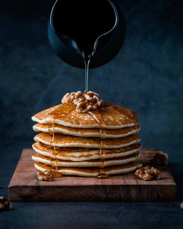 maple syrup pouring onto stack of pancakes with walnuts