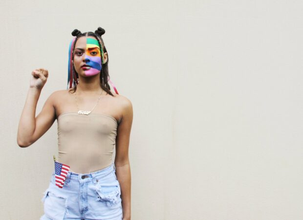 person with face painting of pride flag holding fist for Black Lives Matter movement