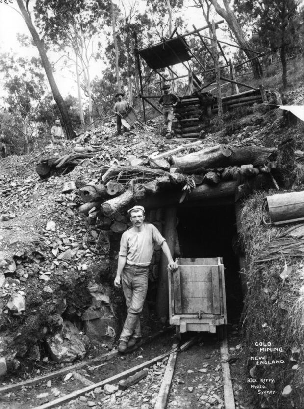 historical black-and-white image of man standing in front of a New England gold mine