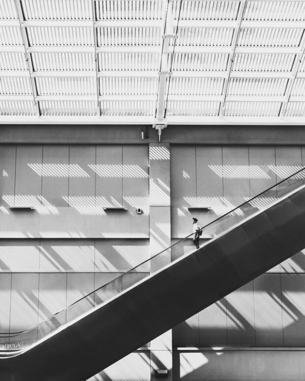 person descending an elevator in black and white