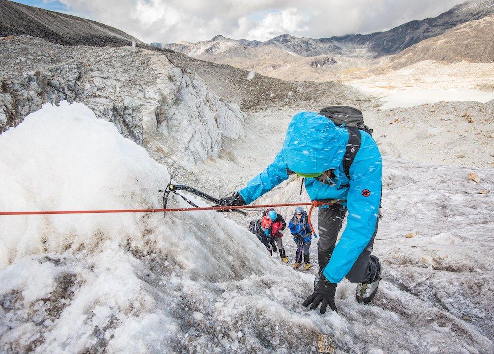Hikers climbing an icy rock face